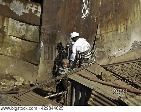 Soweto South Africa, August 15 2007; Woman At Water Pump With Child In Shanty Town Living And Homes