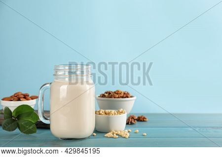 Vegan Milk And Different Nuts On Light Blue Wooden Table. Space For Text