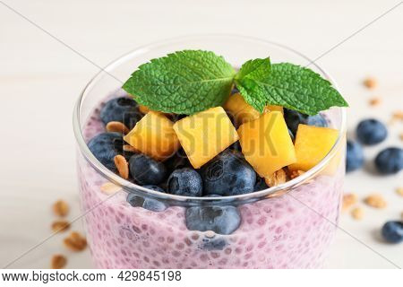 Delicious Chia Pudding With Blueberries, Mango And Mint In Glass On White Table, Closeup