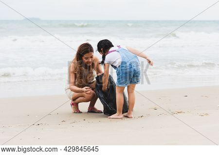Asian Family Volunteers And Children Collecting Garbage On The Beach. Group Of Environmental Help To