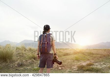 Rear View Of An Asian Photographer Looking At View In The Morning Sunlight With Camera In Hand