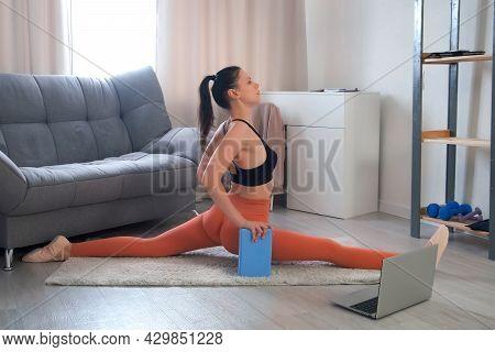 Flexible Sporty Young Woman Making Longitudinal Split Sitting On Carpet. Online Home Fitness, Yoga,