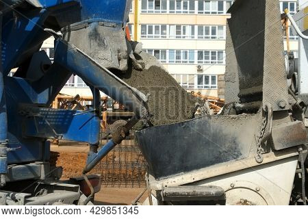 Concrete Is Poured From A Concrete Mixer Into A Metal Container On Construction Site. Cement Truck P