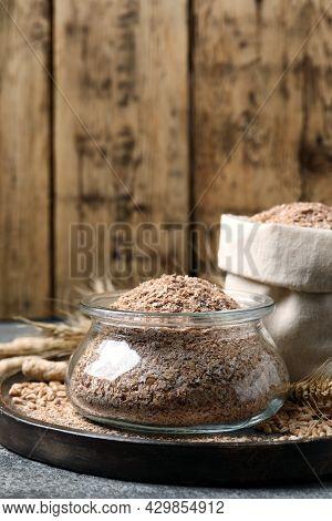 Jar Of Wheat Bran On Grey Table