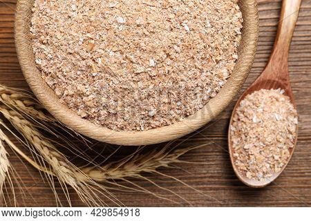 Spoon And Bowl With Wheat Bran On Wooden Table, Flat Lay