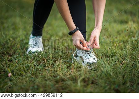 Woman In Sports Clothes Tying Shoelaces At Sneakers. Close Up Of Hands With Smartwatch And Shoes. Co