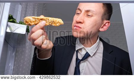 Hungry Overworked Businessman Eats Cucumber With Cakes And Takes Plate Of Snacks In Dark Kitchen At
