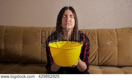 Shocked Brunette Woman In Checkered Shirt Collects Water Flowing From Upstairs Neighbors Into Yellow