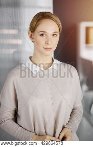 Friendly Adult Casual Dressed Business Woman Standing Straight In Sunny Office. Business Headshot