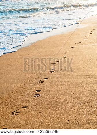 Footprints On Golden Sand By The Sea At Sunset