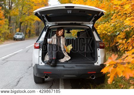 Happy Caucasian Girl Sitting In Suv Trunk And Hold Cup With Tea. Stopping In A Beautiful Place While