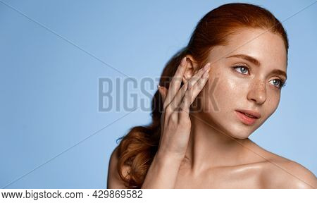Women Wellbeing. Attractive Redhead Girl With Freckles, Touching Smooth, Perfect Clean Skin Without
