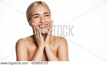 Spa And Cosmetology. Young Blond Woman Smiling Happy, Looking Up, Holding Hands On Face, Apply Moist