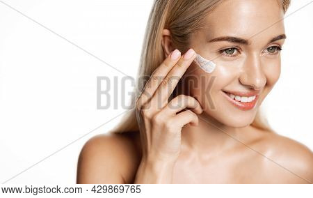 Skin Care And Beauty. Happy Smiling Blond Girl Rub In Moisturizing Cream, Face Lotion Or Cosmetic Ma