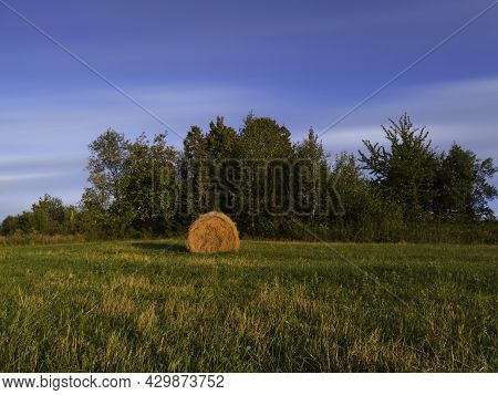 Long Exposure Shot Of Single Round Haystack In The Meadow During Summer Evening, Cattle Fodder In Co