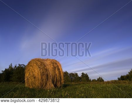 Long Exposure Shot Of Single Round Haystack In The Meadow During Summer Golden Hour At Evening, Catt