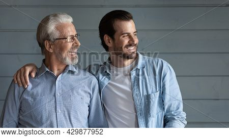 Happy Adult Son And Mature Dad Look In Distance Dreaming