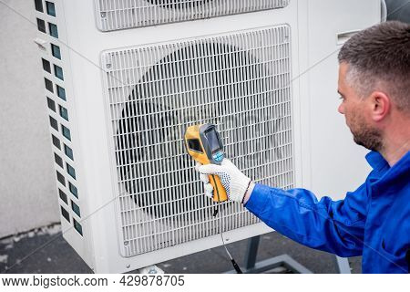 Technician Uses A Thermal Imaging Infrared Thermometer To Check The Condensing Unit Heat Exchanger.