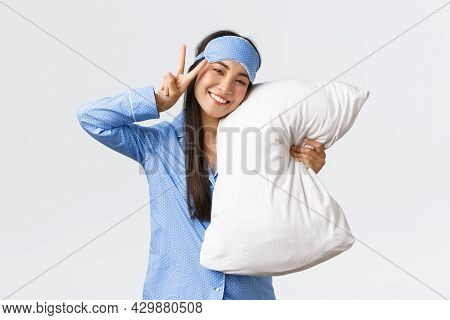 Kawaii Happy Smiling Asian Girl In Blue Sleeping Mask And Pyjama, Hugging Pillow And Showing Peace S