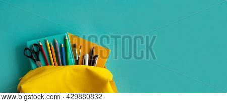 Backpack And School Supplies: Notepad, Pens, Scissors, Book, Watch On Blue Paper Background