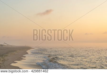 Foggy Sunrise Over The Sea. Pastel Shades. Beautiful Landscape. Sandy Beach Of The Ocean. Sunset Sky