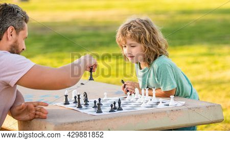 Strategic And Tactic. Tutorship. Dad And Kid Play Logic Game. Father And Son Playing Chess Outside