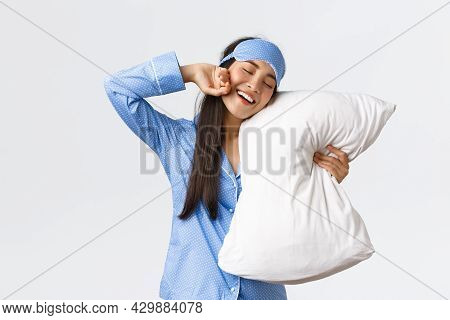 Smiling Pleased Cute Asian Girl In Blue Pyjama And Sleeping Mask, Hugging Pillow And Stretching Hand