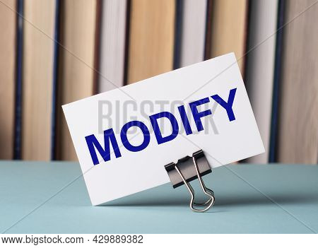A White Card With The Text Modify Stands On A Clip For Papers On The Table Against The Background Of