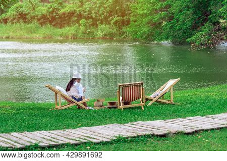 Back View Of Asian Woman With White Hat Sitting On Garden Chair Near Pond In Garden. Summer Vacation