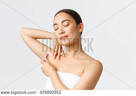 Beauty, Personal Care, And Depilation Concept. Tender Asian Woman In Bath Towel Raising Hand, Shavin