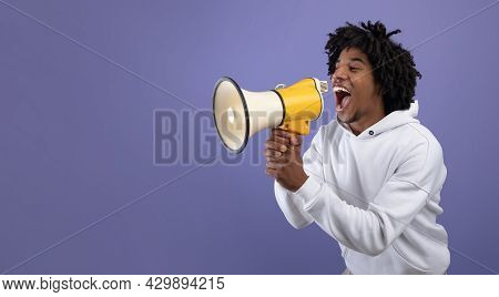 Emotional Black Teen Guy Shouting Into Megaphone, Announcing Breaking News Over Violet Background