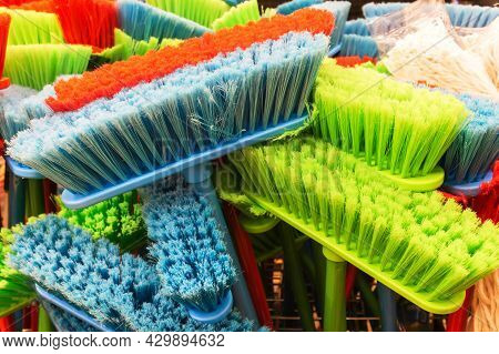 Plastic Brushes. Polymer Brooms Of Different Colors In A Household Goods Store.