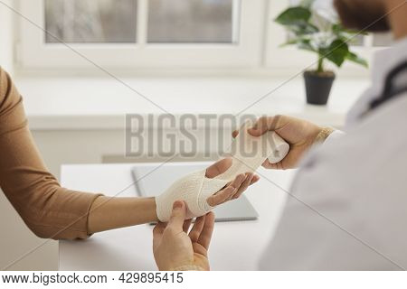 Doctor Or Nurse At Medical Office Wrapping Patients Sprained Wrist With Bandage