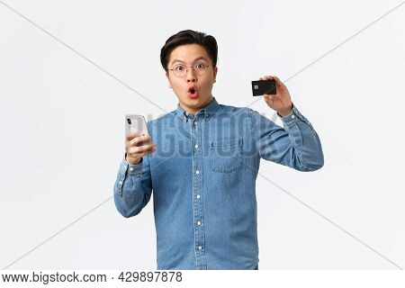 Impressed And Excited Asian Bank Customer, Guy In Glasses And Casual Clothes Showing Credit Card Whi