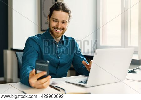 Smiling Young Guy Employee In Casual Wear Looking At Smartphone Screen, Reading Good News In Message
