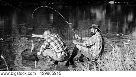 Black Market Caviar. Poachers Fishing. Trap For Fish. Men Sit At Riverside With Fishing Equipment. I