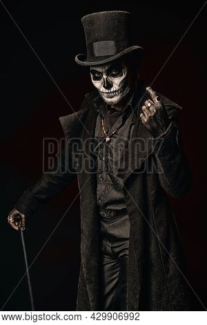 A Young Man In Image Of Baron Samedi, The Voodoo Deity. Baron Saturday In Black Coat And Top Hat Wit
