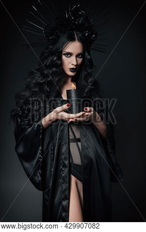 Halloween Theme: Sexy Young Witch Dressed In Black Robe And Headwear With Roses And Spikes. Dark Bea