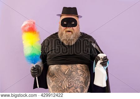 Emotional Plump Man In Hero Suit Holds Brush And Spray Bottle On Purple Background