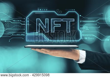 Close Up Of Hand Holding Tablet With Glowing Nft Chip Hologram On Blurry Bokeh Background. Non-fungi
