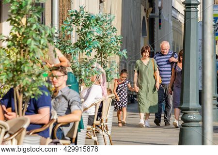 Moscow. Russia. 01 August 2021. Grandparents Walk Hand In Hand With Their Granddaughter Along The Si
