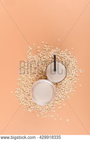 Top View Of Bottle And Glass With Oat Milk On The Oat Flake On Pastel Peach Color Background, Above,