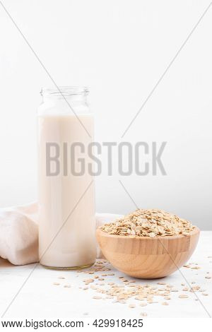 Vegan Non Dairy Alternative Milk. Oat Milk In A Bottle And A Bowl With Oat Flake On White Table Back