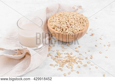 Vegan Non Dairy Alternative Milk. Glass With Oat Milk And A Bowl With Oat Flake On White Stone Table