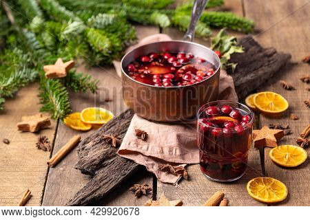 Hot Mulled Red Wine Drink With Citrus, Apples, Cinnamon Sticks, Cloves And Anise In Cooking Pan On W