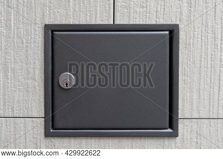 The Safe Door Is On The Wall. Metal Door With A Keyhole On The Wall