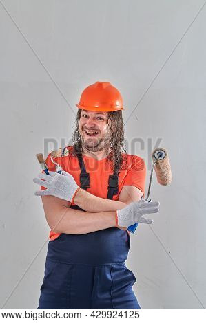 A Professional Builder Stands In Gloves With A Roller And A Brush
