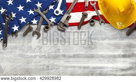 Labor day or American labor concept with construction and manufacturing tools on patriotic US, USA, American flag on white wooden background