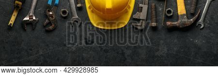 Worn and used work tools with a yellow construction hard hat. Home improvement, Father's day, or Labor day concept.