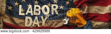 Old US American flag held by a worn work glove holding a crescent wrench with Labor day text. Labor day and American blue collar worker concept.